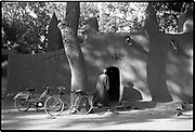 Life is like riding a bicycle; you do not fall off unless you stop pedaling.  Sierra Leonean proverb<br /> <br /> Man parks his bicycle in front of the mosque as he enters for prayers.  Massina, Mali  1994