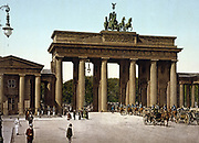The Brandenburg Gate,  Berlin, Germany 1890-1905 , showing carriages with mounted military escort passing through central arch into Unter den Linden. Pedestrians Street Lighting