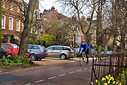 A cyclist riding through Highgate village on 25th March 2007, Highgate, London, United Kingdom. The village is at the top of North Hill with views across London. Until late Victorian times it was a distinct village outside London, sitting astride the main road leading  to the north. Highgate is one of the most expensive London suburbs in which to live and has an active conservation body, the Highgate Society, to protect its character.