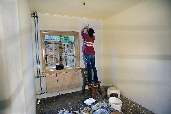 Nederland, Nijmegen, 7-2-2010Een jonge vrouw gebruikt een stoel om op te staan bij het schilderen van een muur in een huis.De woning is gekocht van de woningbouwvereniging Standvast wonen met een aparte regeling, Slimmer Kopen, voor starters.Foto: Flip Franssen/Hollandse Hoogte