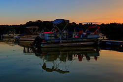 18 July 2014:  Vibrant colors of the seats on a pontoon boat light up in the late afternoon sky at Dawson Lake located in Moraine View State Park maintained by the Illinois Department of Natural Resources (IDNR) near Le Roy Illinois This images has been created in part using High Dynamic Range (HDR) or Panoramic Stitching processes.