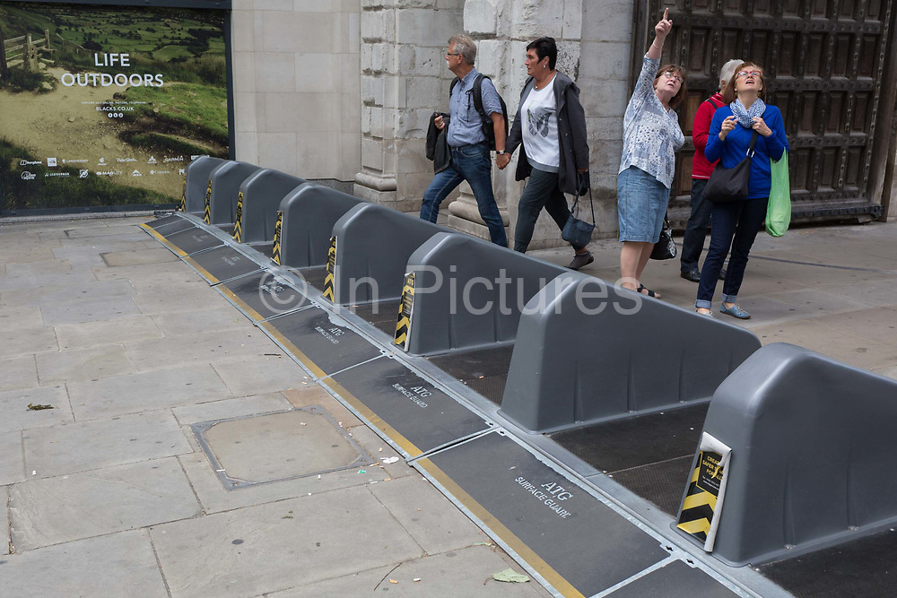 Pedestrians walk over security barriers at one of the entrances to Paternoster Square in the City of London - the capitals financial district, on 4th June 2018, in London, England.