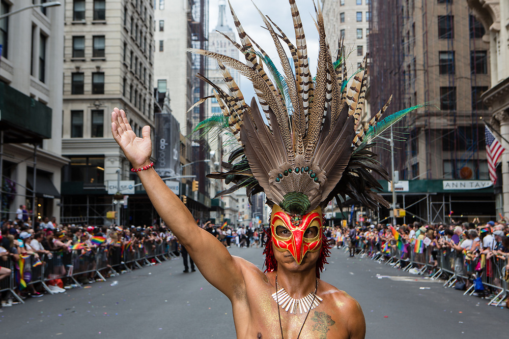 New York, NY - 30 June 2019. The New York City Heritage of Pride March filled Fifth Avenue for hours with participants from the LGBTQ community and it's supporters. A man wears an elaborate mask with tall feathered pkumes.
