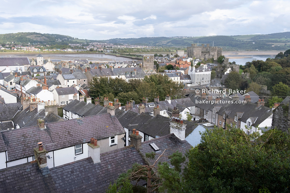 Rooftops of homes located within the medieval walled fortified ramparts of Conwy Castle, on 4th October 2021, in Conwy, Gwynedd, Wales. The walls were constructed between 1283 and 1287 after the foundation of Conwy by Edward I, and were designed to form an integrated system of defence alongside Conwy Castle. The walls are 1.3 km (0.81 mi) long and include 21 towers and three gatehouses. Conwy is a walled market town and community on the north coast of Wales.