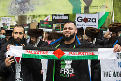 London, UK. 22nd May, 2021. A man holds up a Palestinian scarf as tens of thousands of people take part in the National Demonstration for Palestine. It was organised by pro-Palestinian solidarity groups in protest against Israel's recent attacks on Gaza, its incursions at the Al-Aqsa mosque and its attempts to forcibly displace Palestinian families from the Sheikh Jarrah neighbourhood of East Jerusalem.