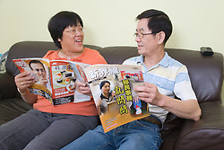 Couple reading Chinese magazines together,