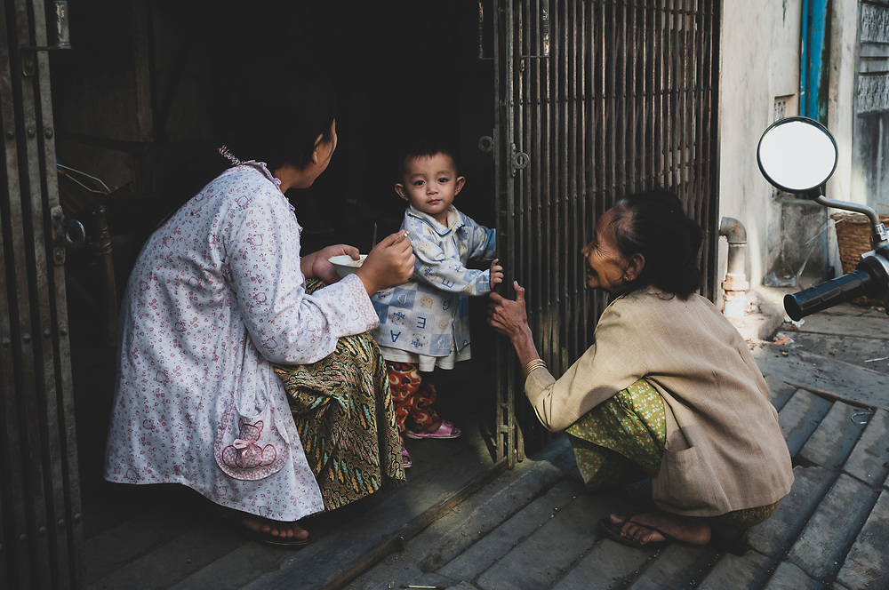 Mandalay, Myanmar - November 9, 2011: A mother feeds her young child in Mandalay.