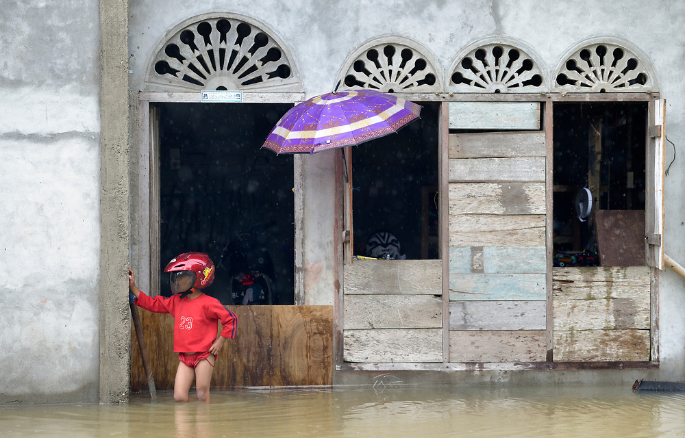 A boy surveys the scene from in front of his flooded house during November 2014 flooding in Meulaboh in Indonesia's Aceh province. Flooding in the region has grown worse because of climate change and the proliferation of palm oil plantations.