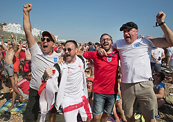 i© Licensed to London News Pictures. 07/07/2018. Brighton, UK. Football fans on the beach in Brighton celebrate England's second goal as they watch a giant TV screen showing England's quarter-final against Sweden from the Russian World Cup. Photo credit: Peter Macdiarmid/LNP