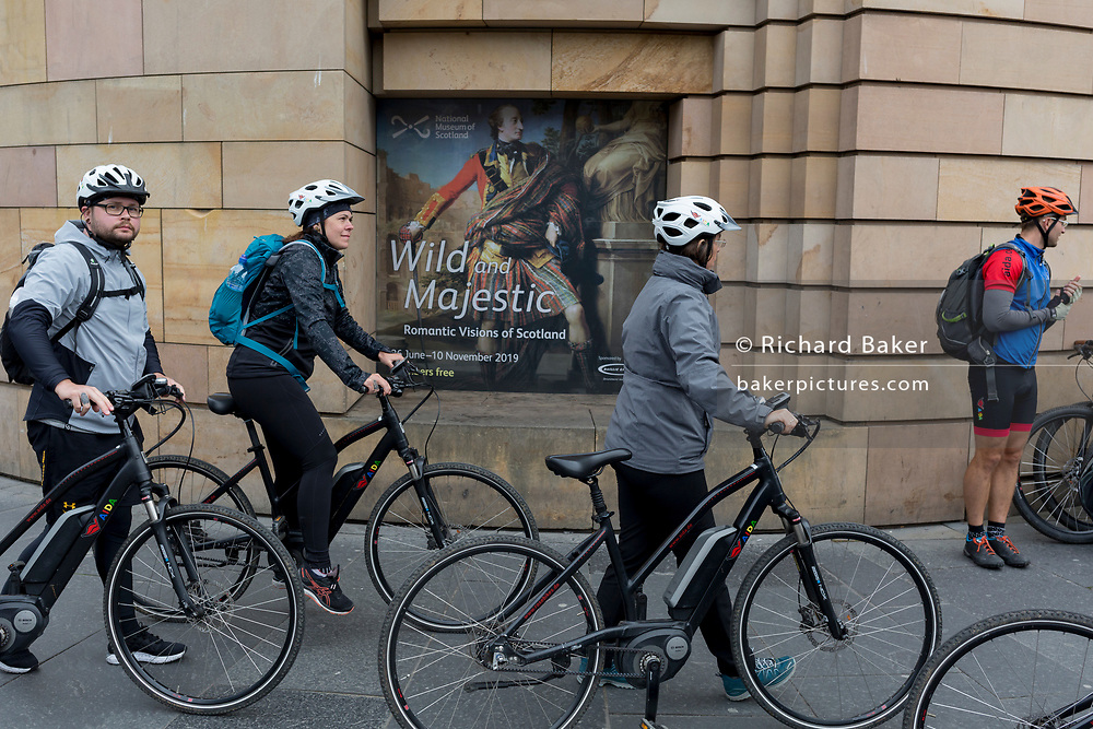 Cycling tourists push their bikes past a poster of Colonel William Gordon of Fyvie by Pompeo Batoni, outside the National Museum of Scotland where the exhibition 'Wild and Majestic' about Scotland's Romantic art movement of the 18th and early 19th century is currently being exhibited, in Edinburgh, on 25th June 2019, in Edinburgh, Scotland.