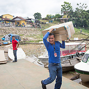 CAPTION: Helpers at the port carry the supplies out to a waiting boat. Dr Neto is in charge of logistics and co-ordination, and ensures that all the boxes are moved through efficiently. LOCATION: Port of Tabatinga, Tabatinga, Amazonas, Brazil. INDIVIDUAL(S) PHOTOGRAPHED: Unknown.