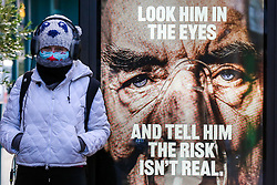 "© L© Licensed to London News Pictures. 29/01/2021. London, UK. A woman wearing a protective face covering walks past the government's 'Look him in the eyes - And tell him the risk isn't real.' publicity campaign poster in north London. Covid-19 infection rates are continuing to drop across London. But health experts are warning Londoners to follow the lockdown rules, as ""any relaxation would risk a rapid reversal or decline."" Photo credit: Dinendra Haria/LNP"