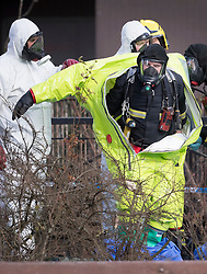 © Licensed to London News Pictures. 08/03/2018. Salisbury, UK. A firefighter is helped from his hazardous material suit after adjusting a police tent covering a park bench next to The Maltings shopping centre in Salisbury where Former Russian spy Sergei Skripaland his daughter Yulia were found after being poisoned with nerve agent. The couple where found unconscious on bench in Salisbury shopping centre. Authorities continue to investigate. Photo credit: Peter Macdiarmid/LNP