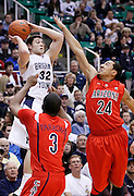 Brigham Young Cougars guard Jimmer Fredette (32) is double teamed by Arizona Wildcats forward Kevin Parrom (3) and guard Brendon Lavender (24)during the first half of an NCAA basketball game, Dec. 11, 2010 in Salt Lake City. (AP Photo/Colin E Braley)