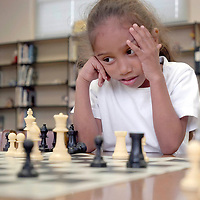Henderson Elementary School student Lisa Brooks, 7, is worried about her next move while participating in the Chess Club.  (Photo by Kim Christensen)