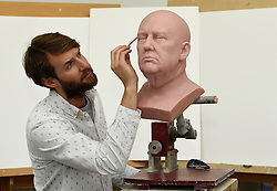 Principal Sculptor David Gardner works on an unfinished wax figure of President-elect Donald Trump at the Madame Tussauds studio in west London, which will be released in January.