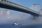 small boat in the fog under Manhattan bridge