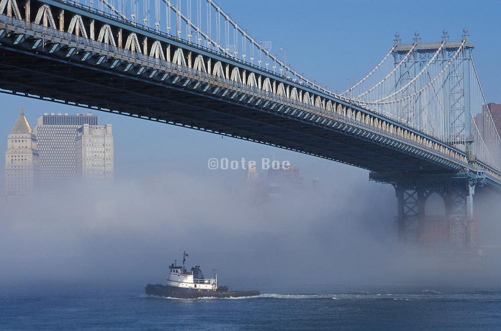 small boat in the fog under Manhattan bridge
