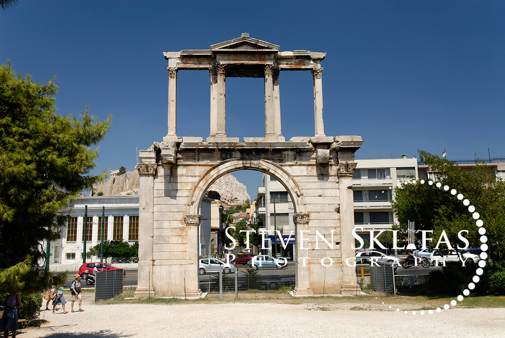 """Hadrian's Arch. Athens. Greece. View of the Arch of Hadrian, a gateway of Pentelic marble built by Roman Emperor Hadrian in 132 AD.  The Arch marked the limit of the old city and the new city of Hadrian. It bears two contrasting inscriptions on each façade. One inscription, facing the Acropolis says """"This is Athens, the ancient city of Theseus"""". The other inscription, in picture, says """"This is the city of Hadrian and not of Theseus""""."""