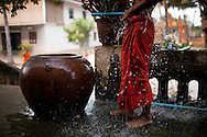 Mid body picture of a monk wearing a traditional orange robe and washing himself. Water flows over his body. Cambodia, Asia