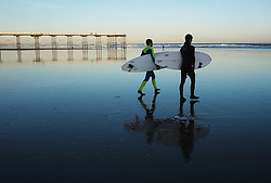 © Licensed to London News Pictures. <br /> 04/01/2015. <br /> <br /> Saltburn, United Kingdom<br /> <br /> Surfers walk across the beach as they go for a morning surf on a freezing cold start to the day in Saltburn, Cleveland.<br /> <br /> Photo credit : Ian Forsyth/LNP