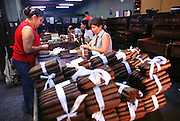 HAVANA, CUBA: Workers at a quality control inspection station in the Partagas Cigar Factory in Havana, Cuba. Wealthy people prize Cuban cigars as the symbol of a fine smoke and revolutionaries favor them because of the cigar?s traditional tie to Fidel Castro.  Photo by Jack Kurtz