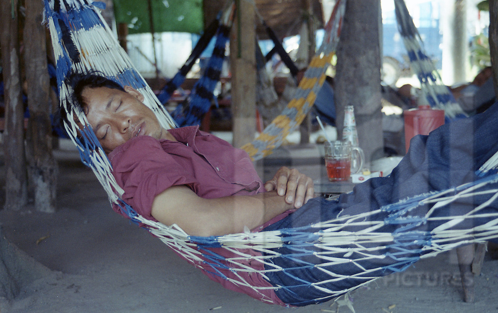 A Man naps in a hammock during the afternoon, Ho Chi Minh city, Vietnam, Asia
