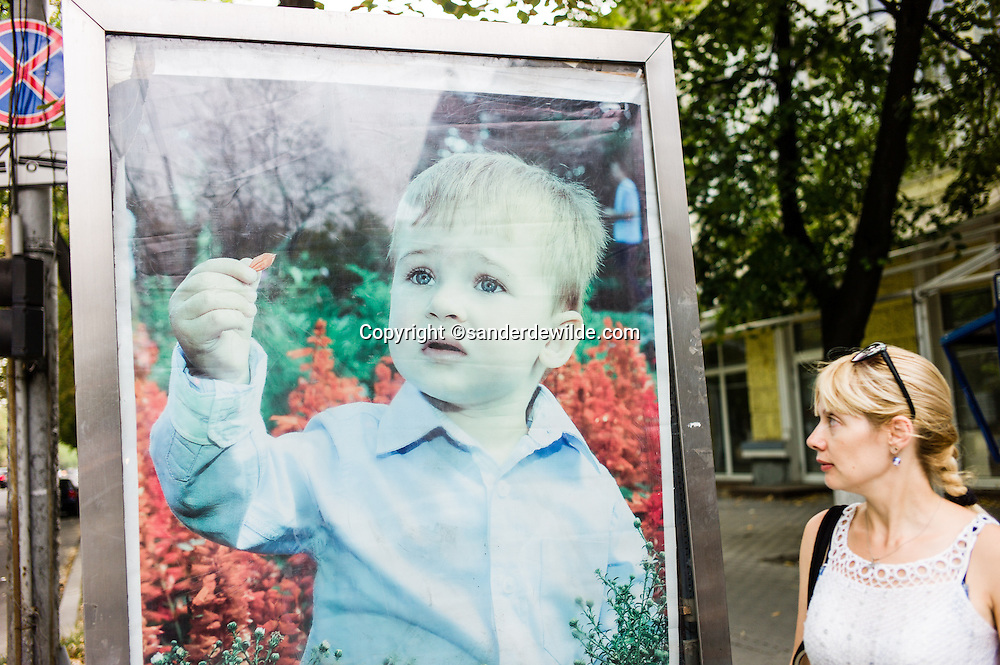 20150814 Chisinau Moldova, a woman walks in the mainstreet of Chisinau passing a lifesize poster of a boy holding the leaf of a flower