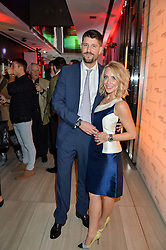 TV Presenter LAURA HAMILTON and her husband ALEX GOWARD at the launch of the new Ferrari 488 Spider held at Watches of Switzerland, 155 Regent Street, London on 25th February 2016.