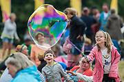 Children continue to have fun with bubbles - The 2017 Latitude Festival, Henham Park. Suffolk 16 July 2017