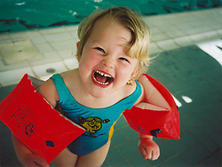 Three year old girl having a swimming lesson wearing armbands