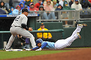 April 12, 2009:  Coco Crisp #2 of the Kansas City Royals slides into third base with a triple as third basemen Cody Ransom #12 of the New York Yankees fields the ball at Kauffman Stadium in Kansas City, Missouri.