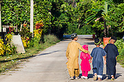 26 OCTOBER 2012 - PULASAIZ, NARATHIWAT, THAILAND: Children walk down the road in front of the mosque during Eid al-Adha services in the villiage Pulasaiz, in the province of Narathiwat, Thailand. Eid al-Adha, also called Feast of the Sacrifice, is an important religious holiday celebrated by Muslims worldwide to honor the willingness of the prophet Ibrahim (Abraham) to sacrifice his firstborn son Ishmael as an act of submission to God, and his son's acceptance of the sacrifice before God intervened to provide Abraham with a ram to sacrifice instead. In 2012 Eid al-Adha was celebrated Oct 25 - 26.     PHOTO BY JACK KURTZ