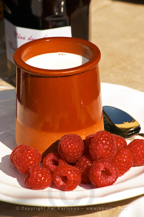 Pot of yogurt on the breakfast table, ceramic, earthenware, on a white plate with fresh raspberries and pots jars of confiture marmalade jam in the background Clos des Iles Le Brusc Six Fours Cote d'Azur Var France