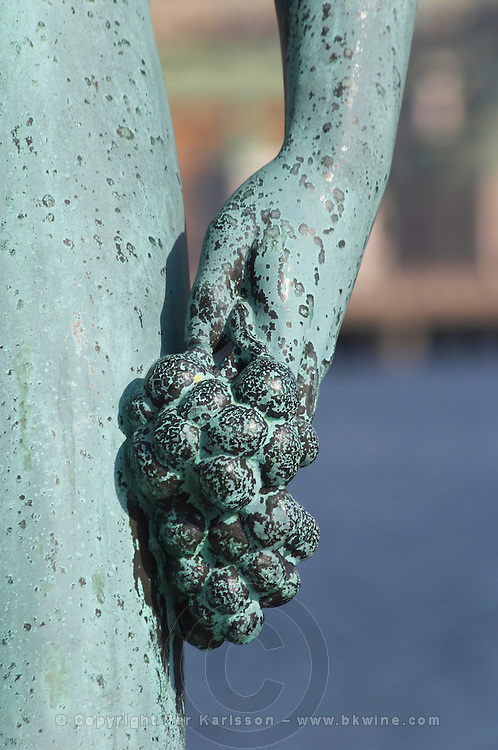 In the Garden of Stadshuset, the Stockholm Town Hall. a bronze statue Song by Carl Eldh a naked man holding a bunch of grapes. In the background the royal palace Closeup of the hand holding the grape bunch Stockholm, Sweden, Sverige, Europe
