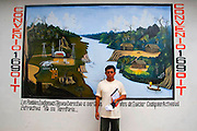 """Ismael Ugkum, """"Apu"""" or leader of a aguaruna community Yamayakatposses for a portrait next to a wall paint that remember the ILO 169 agreement near to Imaza river-port of the Mara-on river in Amazons district, Peru. After the events of June 5 in the Amazonian province of Bagua, in northeastern Peru, where 24 policemen and a number still not confirmed of natives from the communities of the ÒAlto Mara-onÓ and civilians died in clashes after a series of demonstrations in opposition to the approval by the Peruvian government, for a group of ordinances that allow large flexibility in the restrictions on resource extraction in the area, breaking the 169 agreement of ILO (International Labour Organization), which requires the consultation of indigenous communities about the exploitation of nature in their territories. One of the most active communities was the awajun, a warlike and revengeful people, heritors of the Jibaros and recently contacted near to 1950. For the leader or """"apu"""" for one of the aguarunas riverside communities of the Mara-on, Simon Weepiu, Òthe force of this movement come from the conviction of the struggle, which is caused by the ancestral development as based on worldview, which provides the native of a special power, that of becoming one with his idea and his brothers, to focus all on the same objective and be just a great strength."""" The government aims to generate development in the area allowing the exploitation of property, The jungle is rich in gold and oil, and even argue that natural wealth of the region belong to all Peruvians, and not just the communities that inhabit it, but acts as the oil«s filtration to waters of the Mara-on, left in evidence that in a complex ecosystem like jungle that mixed spilled oil by rain in the river, home to fishes, as well as the waters that irrigate cassava, bananas, sugarcane and other elements vital to the development of communities. The natives, insist that the forest is not only home, is where they get medic"""