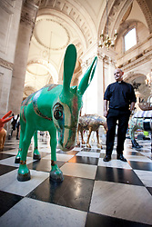 © Licensed to London News Pictures. 30/08/2013. London, UK. Mark Oakley, the Cannon Chancellor  of St Paul's Cathedral, views 25 life-size painted donkeys created by Egyptian artists and placed on display in St Paul's Cathedral, London today (30/08/2013).  The donkeys, created to reflect the common identity of Egyptians, regardless of religion, since the 2011 revolution, are on show to visitors to the cahedral. Photo credit: Matt Cetti-Roberts/LNP