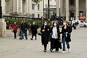 Small group of women wearing face masks walk past the reopened National Gallery as coronavirus lockdown easing continues on 25th May 2021 in London, United Kingdom. Museums and gelleries are now allowed to open once again, as people start to return to normal life.