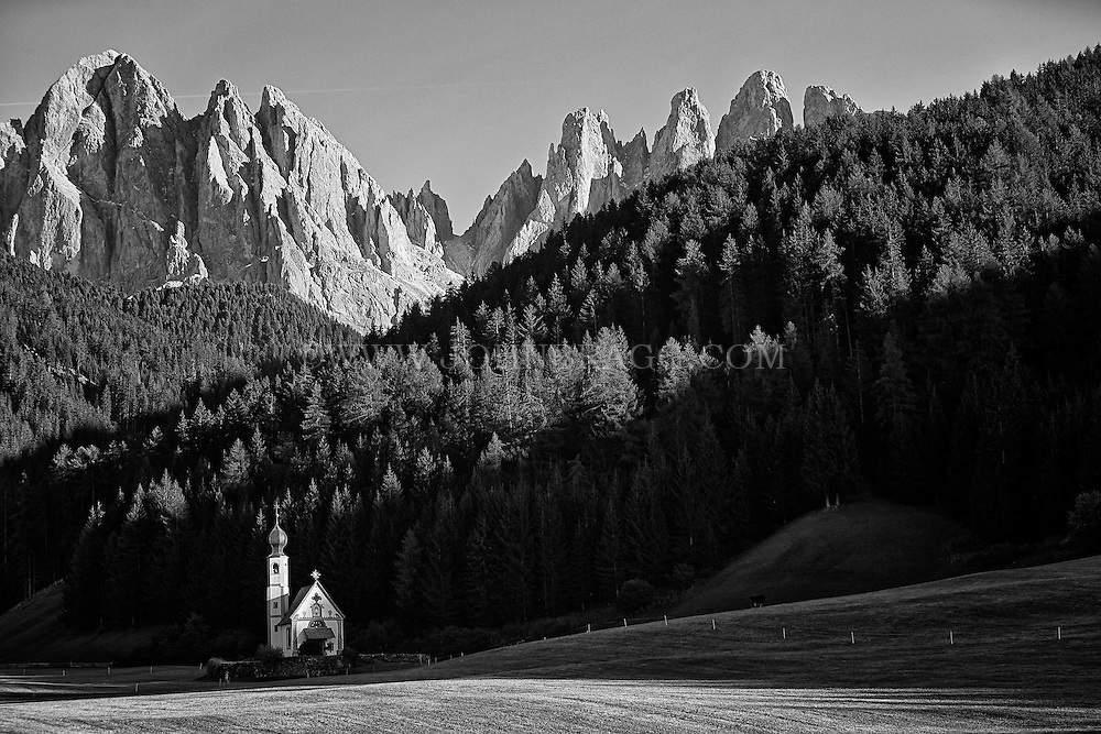 A stunning black and white view of the Dolomites mountain range from a tiny church in St. Magdalena, Italy.