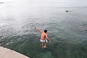 A young boy jumps from a pier into the ocean in Waikiki.