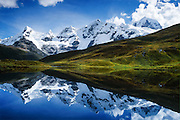 """The Cordillera Huayhuash reflects in a small lake at 15,000 feet in the Andes Mountains, Peru, South America. The highest peak on the right is Siula Grande (east face 20,800 feet or 6344 meters elevation), which was the subject of the gripping 2003 British docudrama """"Touching the Void."""" In 1985, climbers Joe Simpson and Simon Yates scaled the treacherous Siula Grande, one of the last unconquered mountains in the Andes, but after Joe broke his leg, their descent became one of the most amazing survival stories in mountaineering history. This photo shows the northeast face, but they climbed Siula Grande from a valley on the other side (the west face) and descended along the north ridge, on the upper right. The 2003 movie is based upon Joe Simpson's harrowing book, """"Touching the Void: The True Story of One Man's Miraculous Survival."""" At center is the peak of Carnicero (19,550 feet / 5960 meters). Tom Dempsey had this photo published in Wilderness Travel 2006 Catalog of Adventures and in 2009 on Swedish trekking company site www.adventurelovers.se."""