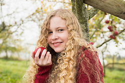 Portrait of a blond teenage girl eating an apple in an apple orchard farm, Bavaria, Germany