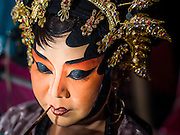 16 JANUARY 2015 - BANGKOK, THAILAND: A performer with the Sai Yong Hong Opera Troupe paints her lips before performing at the Chaomae Thapthim Shrine, a Chinese shrine in a working class neighborhood of Bangkok near the Chulalongkorn University campus. The troupe's nine night performance at the shrine is an annual tradition and is the start of the Lunar New Year celebrations in the neighborhood. Lunar New Year, also called Chinese New Year, is officially February 19 this year. Teochew opera is a form of Chinese opera that is popular in Thailand and Malaysia.    PHOTO BY JACK KURTZ