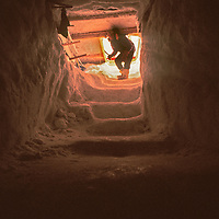 A cook at Adventure Network's Patriot Hills expediton base descends into a snow cave used as a huge outdoor freezer.