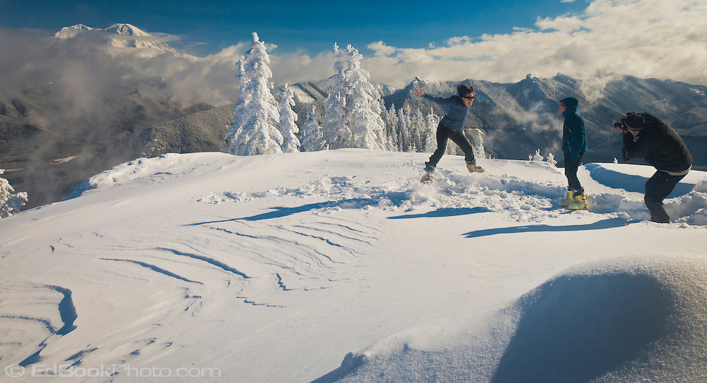 Kelly Pitera returning to earth while levitating at High Hut panorama.  Mount Tahoma Trails non-profit crosscountry ski and snowshoe hut-to-hut trail system on the Tahoma State Forest, with Mount Rainier rising above the Nisqually River Valley in the Washington state Cascade Mountain Range, USA