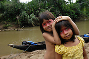 Ecuador, May 9 2010: Huaorani sisters pose for the camera with the river in the background. Copyright 2010 Peter Horrell