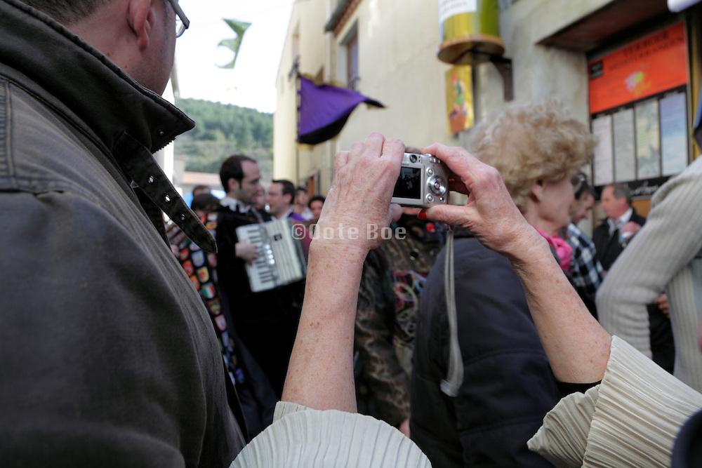 senior woman photographing musicians at street festival Couiza France