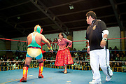 Alicia Flores female wrestler in the ring wrestling a male opponent with referee in shot and crowd in background. Lucha Libre wrestling origniated in Mexico, but is popular in other latin Amercian countries, including in La Paz / El Alto, Bolivia. Male and female fighters participate in the theatrical staged fights to an adoring crowd of locals and foreigners alike.