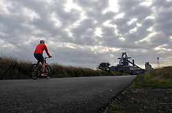 © Licensed to London News Pictures.20/10/15<br /> Redcar, UK. <br /> <br /> A man rides his bike along the road at South Gare in front of the recently closed SSI UK steel blast furnace in Redcar, England. The closure of the site marks the end of 170 years of steel making heritage on Teesside and was the first of a number of recent closures of steel making plants across the UK.<br /> <br /> Photo credit : Ian Forsyth/LNP