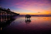 Surfers Looking At The Purple Sky